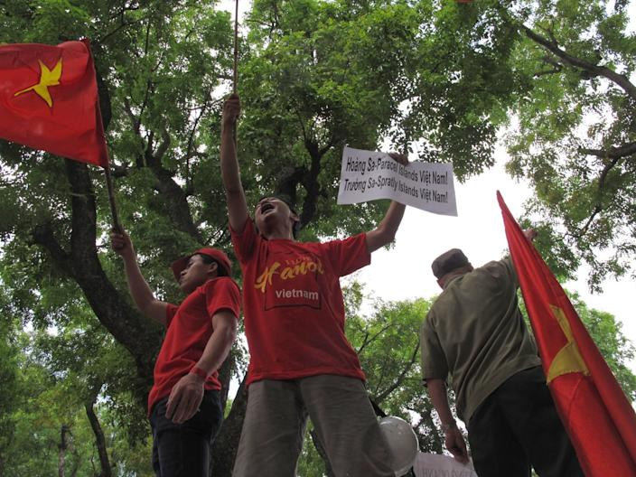 Protesters wave red Vietnamese flags and hold signs