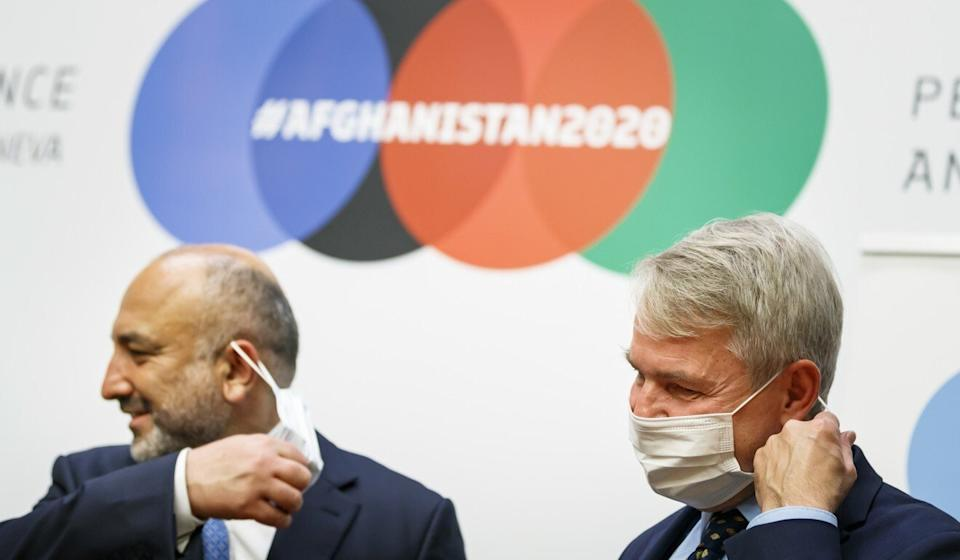 Afghani Foreign Minister Mohammad Hanif Atmar (left) removes his face mask as he stands with Finnish Foreign Minister Pekka Haavisto at a news conference closing the 2020 Afghanistan Conference at the UN's European headquarters in Geneva on Tuesday. Photo: Keystone via AP