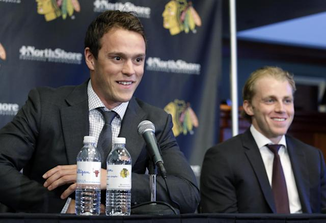 Chicago Blackhawks' Jonathan Toews, left, and Patrick Kane, smile as they listen to the media during a news conference at the United Center in Chicago, Wednesday, July 16, 2014. The Blackhawks recently agreed to eight-year contract extensions with for their star players. (AP Photo/Nam Y. Huh)