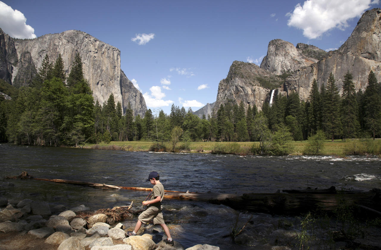 A youngster walks along the banks of the Merced River, in view of El Capitan (L), and Bridalveil Fall (R) in Yosemite National Park, California May 17, 2009. REUTERS/Robert Galbraith