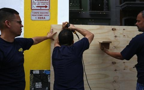 Men cover the entrance of a room with wooden boards in San Juan - Credit: EPA