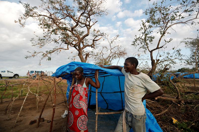 Maria Jofresse, 25, listens while her husband Albano Arnando, 34, chats with neighbors as they stand beside their tent at a camp for displaced people in the aftermath of Cyclone Idai, in John Segredo, near Beira, Mozambique April 2, 2019. (Photo: Zohra Bensemra/Reuters)