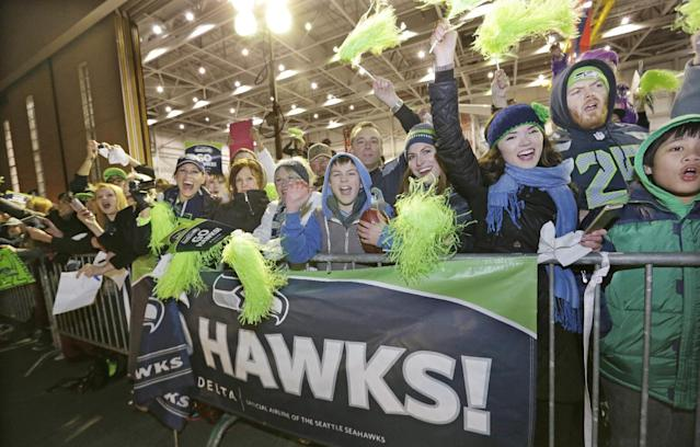 Fans greet Seattle Seahawks players and coaches during the team's arrival at Seattle-Tacoma International Airport, Monday, Feb. 3, 2014, in Seattle. The Seahawks defeated the Denver Broncos 43-8 in the Super Bowl on Sunday. (AP Photo/Elaine Thompson)