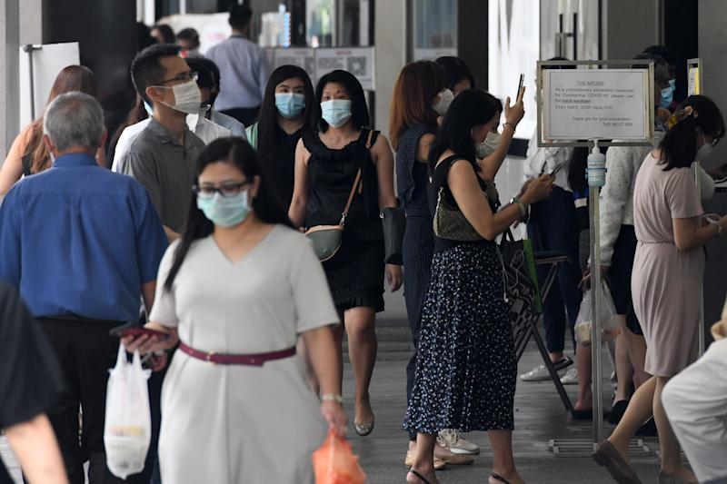 Office workers wearing face masks enter a building during lunch time in the financial business district in Singapore on August 11, 2020. - Singapore's virus-hammered economy shrank almost 43 percent in the second quarter, in a sign that the country's first recession in more than a decade was deeper than initially estimated, official data showed on August 11. (Photo by Roslan RAHMAN / AFP) (Photo by ROSLAN RAHMAN/AFP via Getty Images)