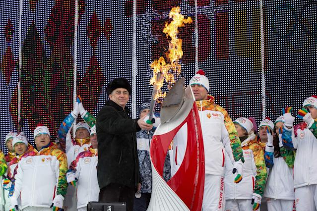 In this photo provided by Olympictorch2014.com, Olympic wrestling champion Aslanbek Khushtov, right, and acting head of Kabardino-Balkaria Yuri Kokov light Olympic flame during a welcome ceremony of the Olympic torch relay in Nalchik, the regional capital of Kabardino-Balkaria province, southern Russia, Thursday, Jan. 30, 2014. The 65,000-kilometer (40,389 mile) Sochi torch relay, which started on Oct. 7, is the longest in Olympic history. The torch has traveled to the North Pole on a Russian nuclear-powered icebreaker and has even been flown into space. (AP Photo/ Olympictorch2014.com)