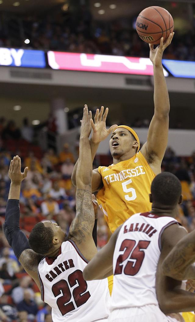 Tennessee forward Jarnell Stokes (5) shoots over Massachusetts forward Sampson Carter (22) and Cady Lalanne during the first half of an NCAA college basketball second-round tournament game, Friday, March 21, 2014, in Raleigh, N.C. (AP Photo/Gerry Broome)