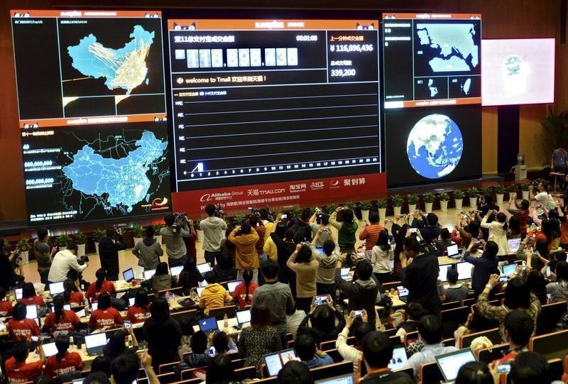 People take pictures of electronic board showing online transaction value on Alipay in Hangzhou