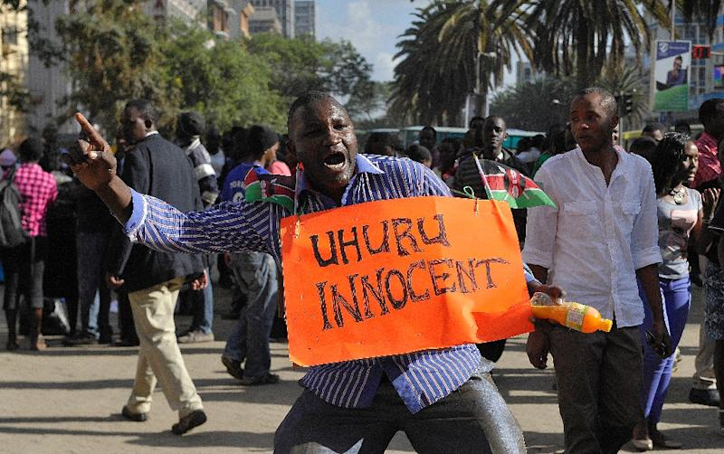 A supporter of Kenya's President Uhuru Kenyatta celebrates in the streets of Nairobi following the ICC ruling to drop crimes against humanity charges against him, on December 5, 2014 (AFP Photo/Simon Maina)