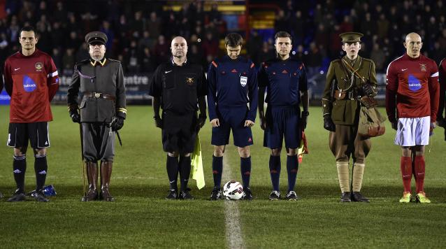 British Army soccer team captain Sergeant Keith Emmerson (R) and his German counterpart, Bundeswehr captain Alfred Hess (L), stand with match officials and mascots wearing World War I uniforms at Aldershot Town FC stadium in Aldershot in south England, December 17, 2014. The two teams were playing each other in a 'Game of Truce' soccer match, commemorating 100 years since the famous peaceful interlude to fighting in World War I when members of the opposing British and German forces played a game of soccer in No Man's Land on Christmas Day 1914. REUTERS/Toby Melville (BRITAIN - Tags: SPORT SOCCER POLITICS ANNIVERSARY CONFLICT MILITARY TPX IMAGES OF THE DAY)