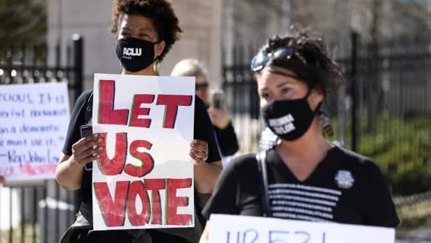 Protesters gathered outside the Georgia State Capitol last month as lawmakers debated several voting bills. Defenders of a now-passed law say it's being badly distorted. (Dustin Chambers/Reuters - image credit)