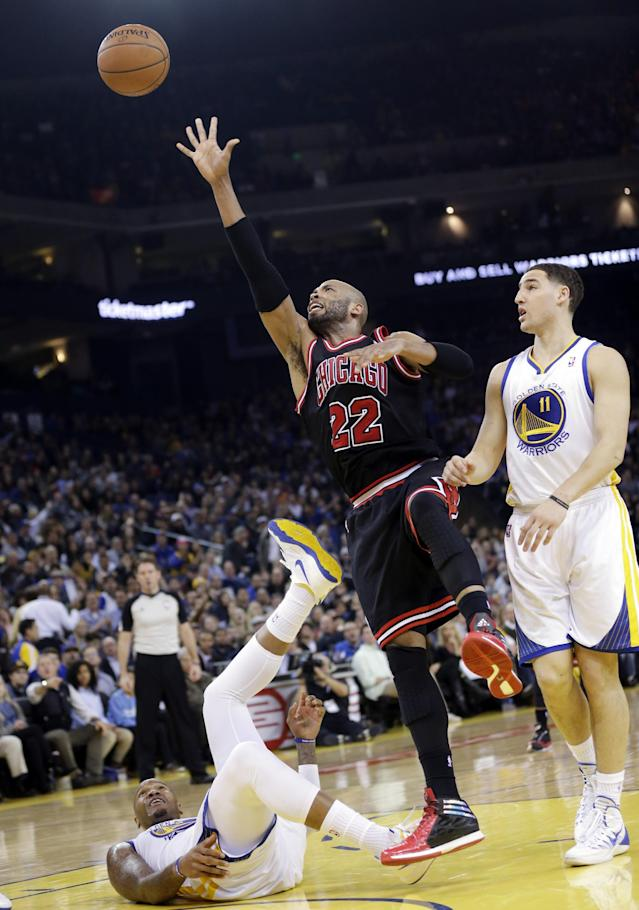 Chicago Bulls' Taj Gibson (22) makes an off balance shot next to Golden State Warriors' Marreese Speights, left, and Klay Thompson (11) during the first half of an NBA basketball game, Thursday, Feb. 6, 2014, in Oakland, Calif. (AP Photo/Marcio Jose Sanchez)