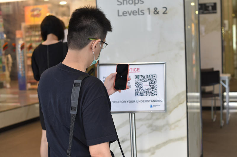 A man scans a QR code before entering a building in Singapore Tuesday, June 2, 2020. Singapore reopened 75 percent of its economy Tuesday, as part of a three-phase controlled approach to end a virus lockdown since early April. (AP Photo/YK Chan)