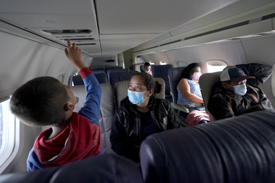 Yancarlos Amaya, 5, left, a migrant from Honduras, explores the instruments above his seat as his mother, Celestina Ramirez, looks on during an airplane ride to Houston, Wednesday, March 24, 2021, in Harlingen, Texas. Even though flying seems luxurious compared to her journey through Central America and Mexico and border detention, Ramirez is still anxious because it's her first time. (AP Photo/Julio Cortez)