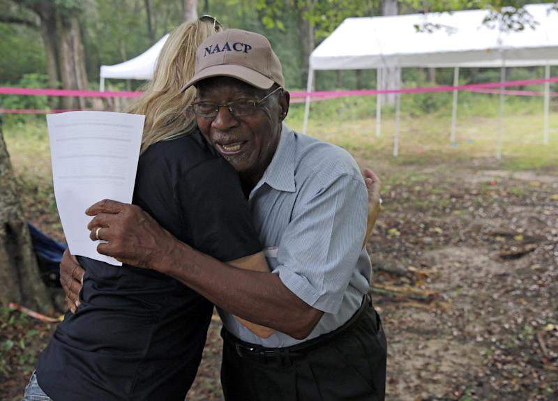 University of South Florida assistant professor Dr. Erin Kimmerle hugs Elmore Bryant on the site of the Boot Hill cemetery where a team of anthropologists from the University of South Florida began exhuming suspected graves on Saturday, Aug. 31, 2013, at the now-closed Arthur G. Dozier School for Boys in Marianna, Fla. The researchers are sifting through topsoil to find remains at the former reform school in hopes of identifying the boys buried there and learning how they died. Bryant is a former Dozier School employee and a former mayor of Marianna. (AP Photo/The Tampa Bay Times, Edmund D. Fountain, Pool)