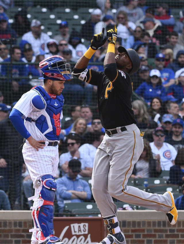 Pittsburgh Pirates' Gregory Polanco, right, points to the sky as he crosses home plate in front of Chicago Cubs catcher Victor Caratini (7) after hitting a home run in the seventh inning of a baseball game, Thursday, April 12, 2018, in Chicago. (AP Photo/Matt Marton)