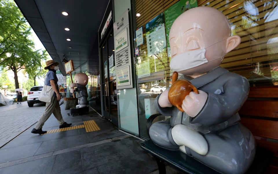 Buddhist monk doll wearing a face mask is displayed near the Chogyesa temple in Seoul - AP