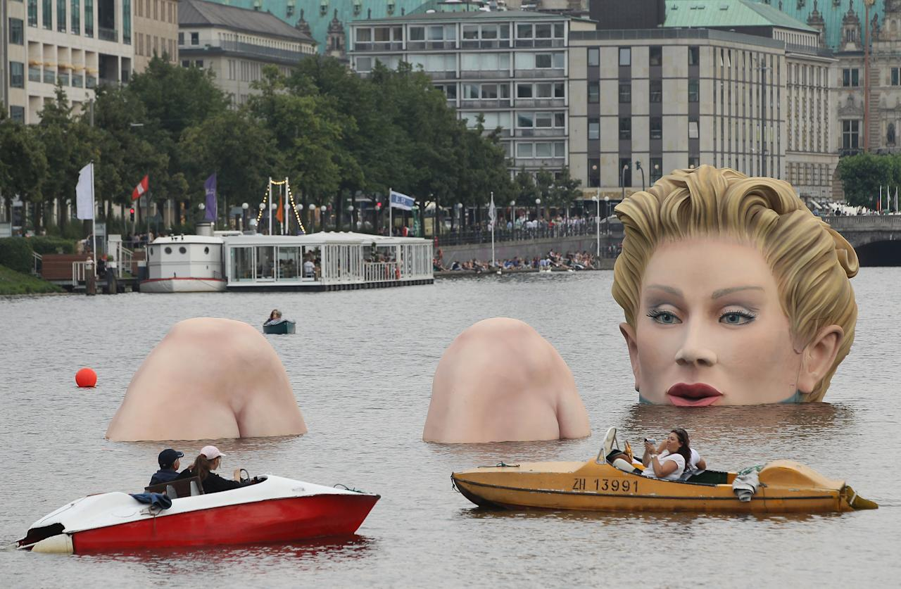"HAMBURG, GERMANY - AUGUST 03:  People in boats approach ""Die Badende"" (""The Bather""), a giant sculpture showing a woman's head and knees as if she were resting in the Binnenalster lake on August 3, 2011 in Hamburg, Germany. The sculpture, which is made of styrofoam and steel and measures 4 meters high and 30 meters long, is a project by artist Oliver Voss and will be on display for the next ten days.  (Photo by Sean Gallup/Getty Images)"