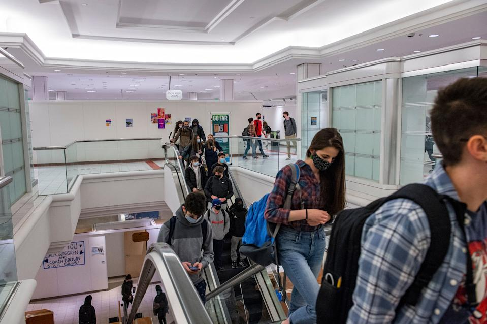 Students from the new Downtown Burlington High School use the building's escalators to get between floors and classes at a closed Macy's department store in Burlington, Vermont on March 30, 2021. - Vermont Macy's was transformed into high school after toxic chemicals closed down Burlington High School building. (Photo by Joseph Prezioso / AFP) (Photo by JOSEPH PREZIOSO/AFP via Getty Images)