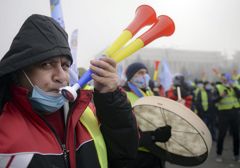 A man blows a horn at a rally of policemen and retired members of the military in Bucharest, Romania, Tuesday, Feb. 23, 2021. Hundreds of Romanian policemen have marched in protest of planned austerity measures that envisage freezing of salaries in the public sector.(AP Photo/Alexandru Dobre)