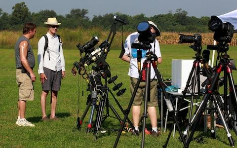 A group of eclipse fans set up their tripods as they wait for the beginning of the solar eclipse  - Credit: Reuters