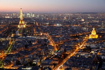FILE PHOTO: A general view shows the illuminated Eiffel Tower, the Hotel des Invalides and rooftops at night in Paris
