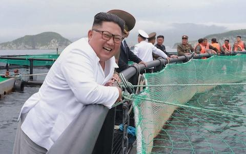 The North Korean leader's mood appeared to have improved during his visit to the Rajin salmon - Credit: AFP