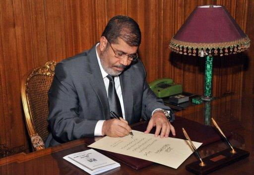 Mohamed Morsi in Cairo on December 26, 2012, as he signs into law a new constitution