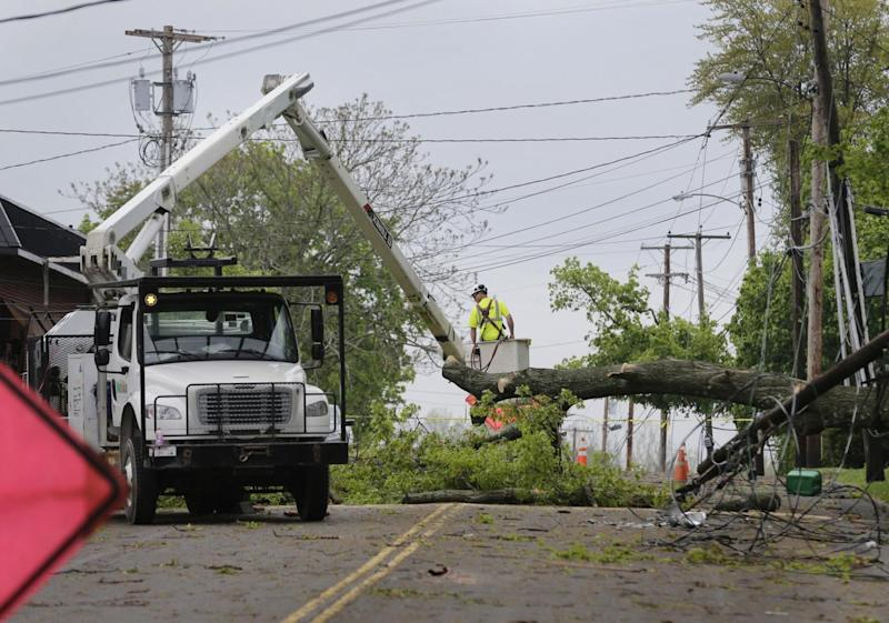 Crews work to clear a road cover in debris following a storm in Newburgh, New York (AP)