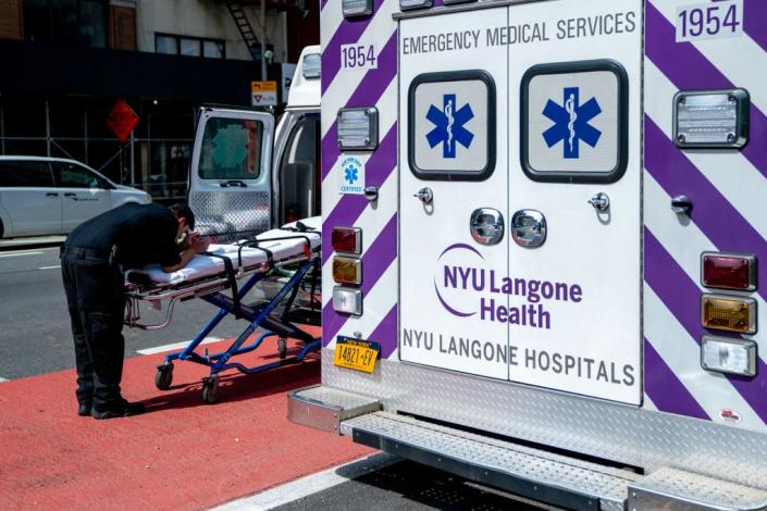 """<div class=""""inline-image__caption""""><p>A EMT takes a moment in front of NYU Langone Hospital on April 7.</p></div> <div class=""""inline-image__credit"""">David Dee Delgado/Getty</div>"""