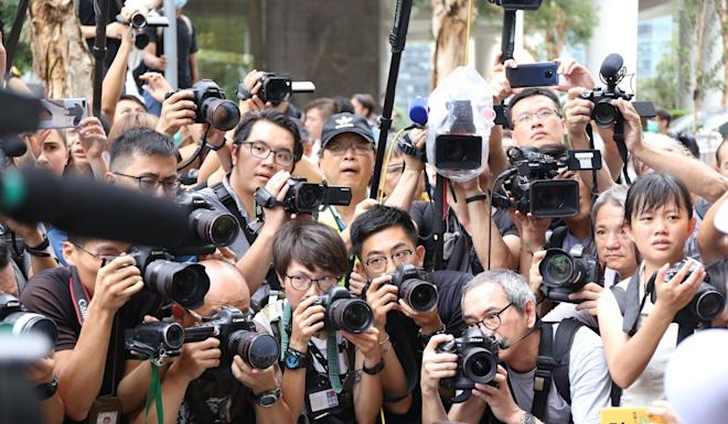 Photographers take pictures of an anti-extradition bill protester outside the British consulate in June 2019. Photo: Rachel Cheung