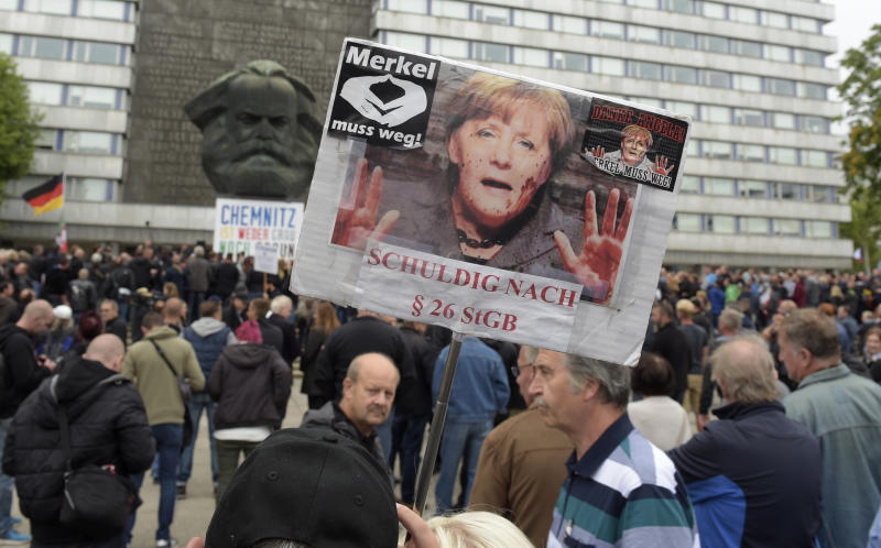"A protestor holds a poster with a photo of Angela Merkel reading 'Merkel must go"" and referring she is guilty of incitement in Chemnitz, eastern Germany, Saturday, Sept. 1, 2018, after several nationalist groups called for marches protesting the killing of a German man last week, allegedly by migrants from Syria and Iraq. (AP Photo/Jens Meyer)"