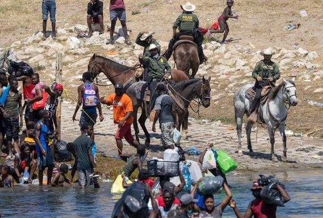 CIUDAD ACUNA, MEXICO - SEPTEMBER 20: U.S. Border Patrol agents interact with Haitian immigrants on the bank of the Rio Grande in Del Rio, Texas on September 20, 2021 as seen from Ciudad Acuna, Mexico. As U.S. immigration authorities began deporting immigrants back to Haiti from Del Rio, thousands more waited in a camp under an international bridge in Del Rio while others crossed the river back into Mexico to avoid deportation. (Photo by John Moore/Getty Images) (Photo: John Moore via Getty Images)