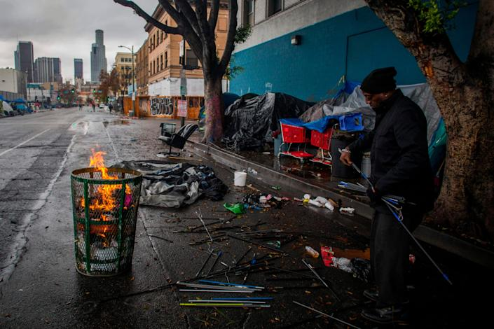 A homeless man makes a fire from trash to keep warm on Thanksgiving Day in Los Angeles. The Supreme Court was asked to let cities criminalize homelessness.