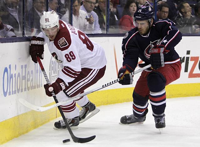 Columbus Blue Jackets' James Wisniewski, right, tries to steal the puck from Phoenix Coyotes' Mikkel Boedker, of Denmark, during the first period of an NHL hockey game Tuesday, April 8, 2014, in Columbus, Ohio. (AP Photo/Jay LaPrete)