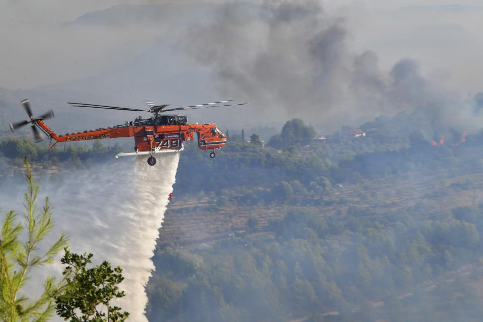 An helicopter drops water during a wildfire in ancient Olympia, western Greece, Thursday, Aug. 5, 2021. Greece evacuated people in boats from an island beach Wednesday amid heavy smoke from a nearby wildfire and fire crews fight elsewhere to keep flames away from the birthplace of the ancient Olympic Games as the country sweltered under a record heat wave. (Giannis Spyrounis/ilialive.gr via AP)