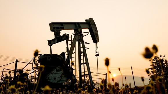A pump jack in a medow with the sun setting in the distance.