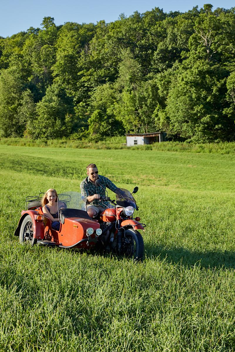 Graham and ten Have ride a motorcycle with sidecar on the property.