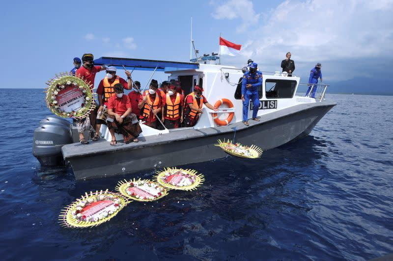 People throw flowers and petals with names of the sunken KRI Nanggala-402 submarine crew members from the boat during a prayer at the sea