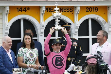 May 18, 2019; Baltimore, MD, USA; Jockey Tyler Gaffalione holds the Woodlawn Vase in the Winner's Circle after winning the 144th running of the Preakness Stakes aboard War of Will (not pictured) at Pimlico Race Course. Geoff Burke-USA TODAY Sports