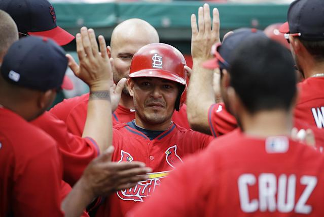 St. Louis Cardinals' Yadier Molina high-fives teammates after scoring off a single by Peter Bourjos in the first inning of an exhibition spring training baseball game against the Miami Marlins, Tuesday, March 25, 2014, in Jupiter, Fla. (AP Photo/David Goldman)