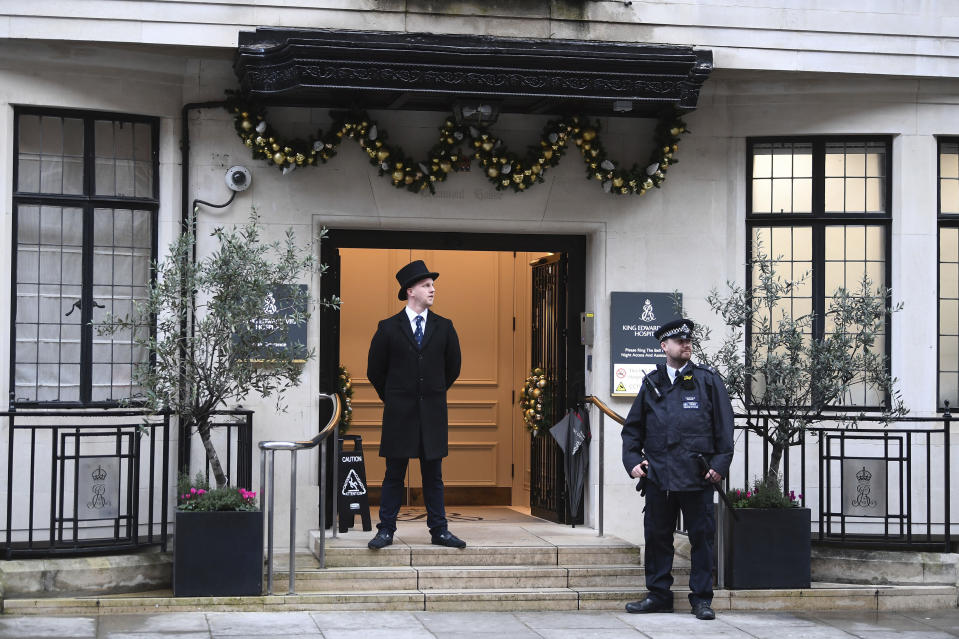 """Police and hospital personnel outside King Edward VII's Hospital, in London, Friday, Dec. 20, 2019. Prince Philip, husband of Queen Elizabeth II, has been admitted to a London hospital """"as a precautionary measure,"""" Buckingham Palace said Friday. The palace said in a statement the 98-year-old Philip was admitted to the King Edward VII hospital for observation and treatment of a pre-existing condition.  (Victoria Jones/PA via AP)"""