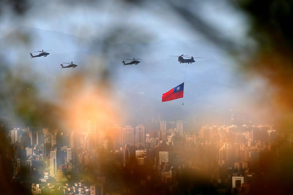 A military helicopter carrying a Taiwan flag flies over Taipei on October 5 as part of the rehearsal ahead of a day of celebration, amid China's growing military threats. Source: Getty