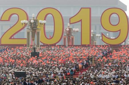 People wave Chinese flags before a military parade marking the 70th founding anniversary of People's Republic of China, on its National Day in Beijing