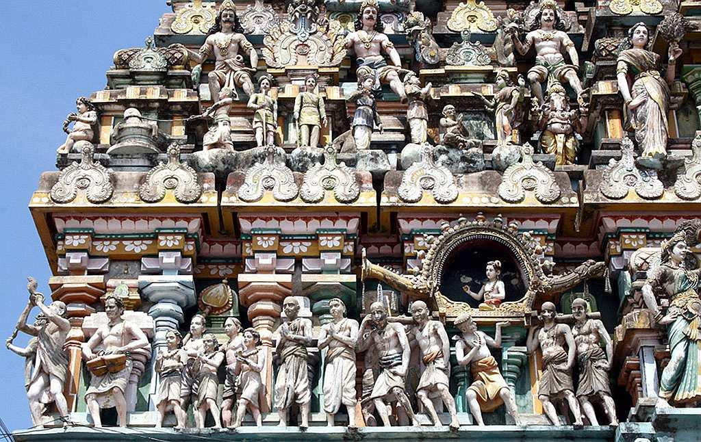 A temple relief depicting Appar bearing Sambandar's palanquin at Thirukadaiyur Temple, Tamil Nadu. This is one of the Ashta Veeratta sthalams -- the eight places where Lord Shiva materialized in his furious aspect -- and here Lord Shiva saved Markandeya from Yama, the god of death. This temple belongs to Dharmapuram Aadinam (Mutt). This temple deities are sung of by the Tamil trinity, i.e, Appar, Sundarar and Thirugnana Sambandar. The presiding deity is Amruthakadeswarar. His consort is Abhirami. Abhirami Andhathi was written here by Abhirami Bhattar. The temple is in line with the grand temple architecture of the Cholas and occupies a vast area of 11 acres with five Prakarams, imposing temple towers and large and spacious Mandapams. In the figural gopuram, the story of close association of Appar (bearing palanquin) and Thirugnana Sambandar (sitting in the palanquin) is well depicted. Thirukadaiyur is about 15 km from Karaikal.