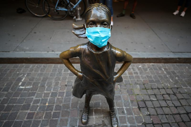 NEW YORK, USA - MAY 26: The Fearless Girl Statue with a face mask on which across the New York Stock Exchange (NYSE) building is seen during Covid-19 pandemic in Lower Manhattan, New York City, United States on May 26, 2020. Wall Street trading floor partially reopening after coronavirus pandemic shutdown. (Photo by Tayfun Coskun/Anadolu Agency via Getty Images)