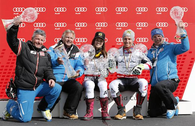 Austria's Marcel Hirscher, second from right, and Anna Fenninger, center, pose with members of the Austrian ski team as they hold their overall leader trophies, at the alpine ski World Cup finals in Lenzerheide, Switzerland, Sunday, March 16, 2014. (AP Photo/Armando Trovati)
