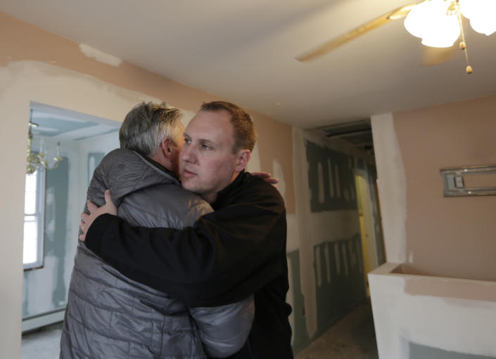 Donald Denihan, left, embraces firefighter Chris Troy during a visit to the Troy family house, under renovation after it was seriously damaged during Superstorm Sandy, in Long Beach, N.Y., Wednesday, Dec. 12, 2012. The Troys are living in a house in Point Lookout, N.Y., donated by strangers who found them. Denihan, who suffered near-death experiences that convinced him his purpose in life was to help others, is paying for renovations to the Troy's home. He has instructed his workers to have the house ready by Christmas. (AP Photo/Kathy Willens)