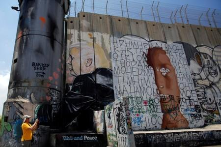 A man takes pictures near the Israeli barrier with a mural depicting U.S. President Donald Trump, in Bethlehem, in the Israeli-occupied West Bank