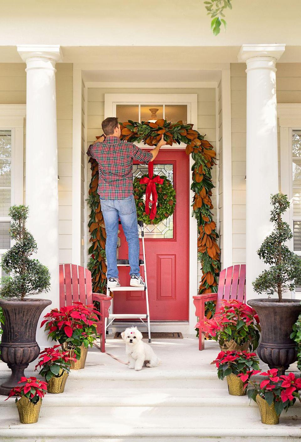 """<p>A fuss-free entryway crafted by Ashley Brooke of <a href=""""https://ashleybrookedesigns.com/"""" rel=""""nofollow noopener"""" target=""""_blank"""" data-ylk=""""slk:Ashley Brooke Designs"""" class=""""link rapid-noclick-resp"""">Ashley Brooke Designs</a> features signature holiday blooms with poinsettias wrapped in gold. </p>"""