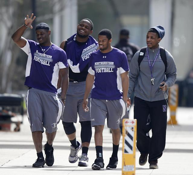 Unidentified Northwestern football players walk between their locker room and McGaw Hall, where voting is taking place on the student athlete union question Friday, April 25, 2014, in Evanston, Ill. Northwestern football players cast secret ballots Friday in an on-campus hall adjacent to their home stadium on whether to form the nation's first union for college athletes. (AP Photo/Charles Rex Arbogast)